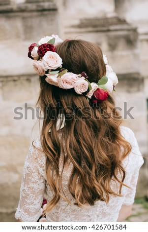 Wedding decoration. Fresh delicate magical wedding wreath pink roses and red peonies on beautiful bride close-up.  - stock photo