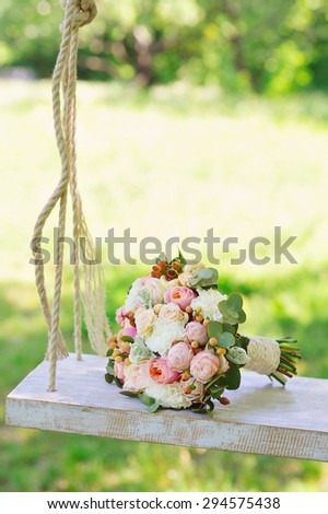 Wedding decoration of a beautiful delicate bouquet lying down on a swing in the park against green background - stock photo