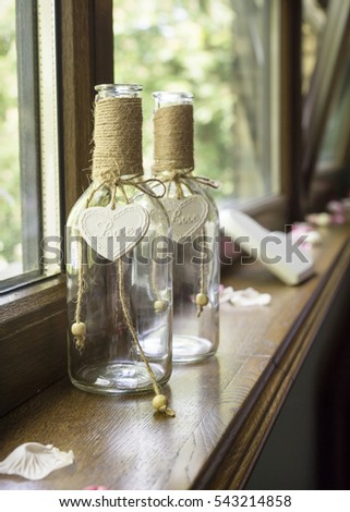 Wedding decoration of two bottle with hearth and love sign on a window.