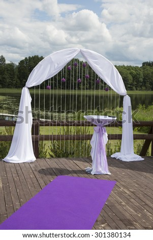 wedding decorations: arch and table before ceremony - stock photo