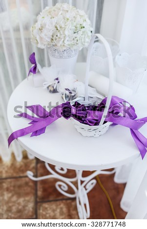 Wedding decorations in restaurant. Basket with violet ribbons.