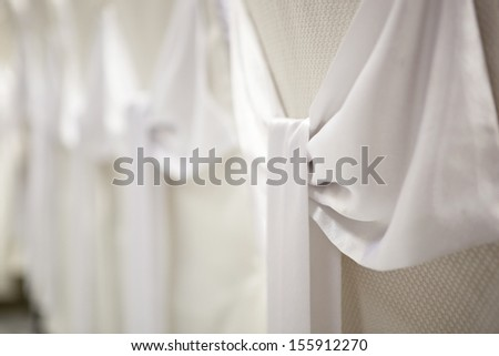 wedding decorations - white satin bows on the chair covers