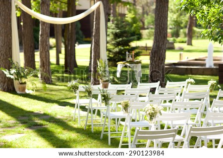 Wedding decorations with flowers. Flowers in a mason jar at a wedding ceremony. Seating guests. Wedding ceremony. - stock photo