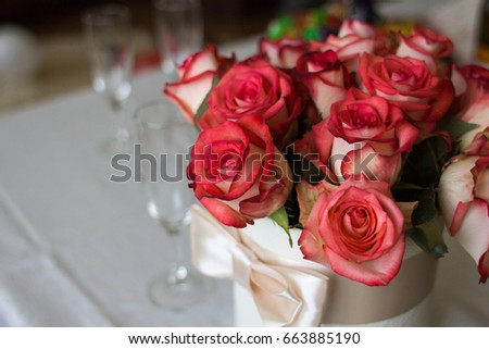 Wedding details. A bouquet of roses in a hat box and glass goblets