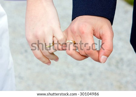 wedding details - closeup of holding man's and woman's hands wearing wedding ring - stock photo