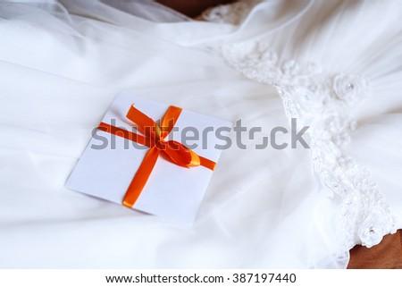 Wedding Details. Invitation Lying on Wedding Dress. - stock photo