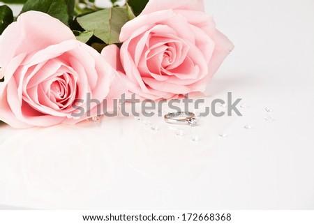 Wedding diamond ring with pastel pink roses - stock photo