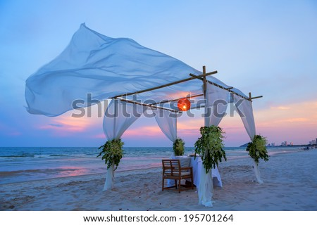 Wedding dinner setting on the beach at twilight - stock photo