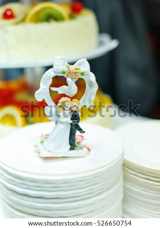 wedding dolls posing with dove for wedding cake with bokeh background