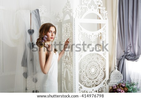 Wedding dress fashion. Beautiful young bride in vintage wedding dress indoors. White wedding dress at model. Girl shows wedding fashion in decorated shabby chic interior with flowers, high key.  - stock photo
