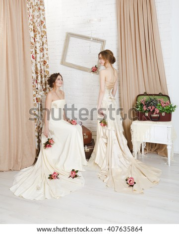 Wedding dress fashion. Two beautiful young brides in vintage wedding dresses indoors. Rustic wedding dresses at models. Girls in champaigne color dresses in decorated interior with flowers, high key.  - stock photo