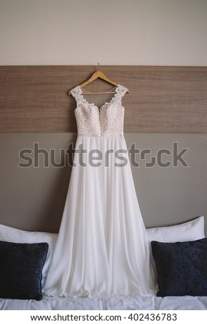 wedding dress hanging over the bed in hotel room during the bride preparation