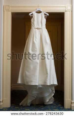 wedding dress hanging up by the door