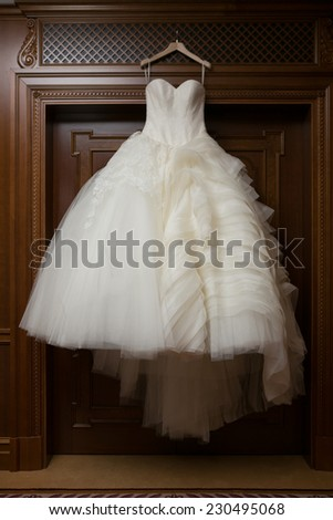 wedding dress hanging up by the window - stock photo