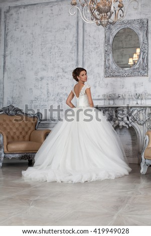 Wedding dress in Paris. Bride in a luxury apartment in a wedding dress. Bride near the window and the fireplace