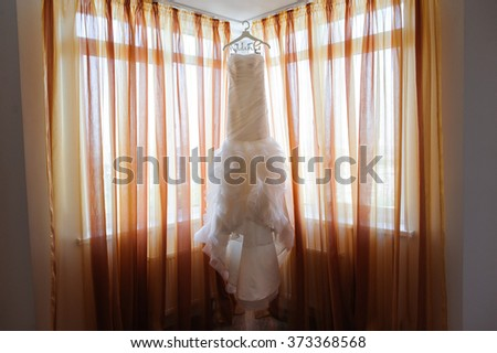 Wedding dress of the bride hanging on a hanger near a window