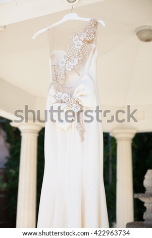 Wedding dress on a wooden hanger. Piano.