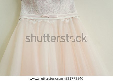 Wedding Dress pink hanging on a hanger. Close-up.