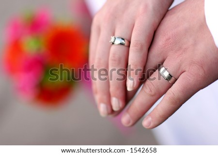 wedding engagement with two hands, their rings, and flowers in the background