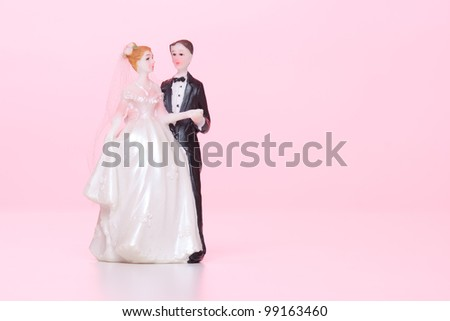 Wedding figurines (bride and groom) on pink background. - stock photo