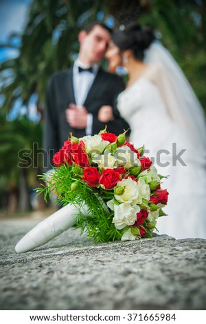 Wedding flowers bouquet with newlywed couple on background - stock photo
