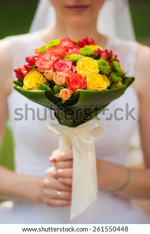 wedding flowers. close-up. beautiful young bride with wedding bouquet in hands. close up woman holding flowers. vertical photo. wedding day.  - stock photo