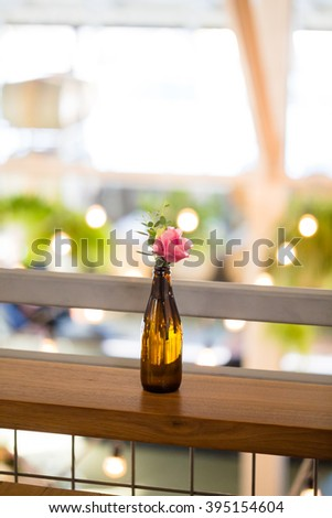 Wedding flowers on reception tables setup by a florist using vintage antique bottles. - stock photo