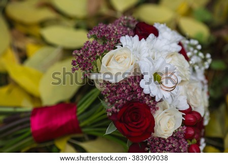 wedding flowers, wedding rings lie on a wedding bouquet, bouquet of red and peach, dairy roses and white flowers lying on yellow autumn leaves, wedding ceremony, come autumn, time of year - stock photo