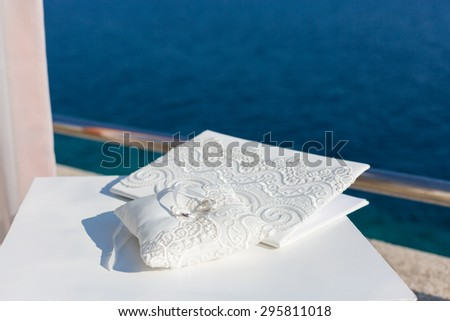 wedding folder and pillow with rings - stock photo