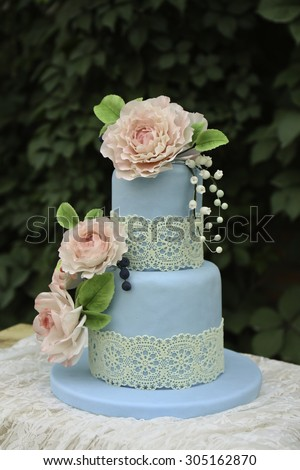 Wedding fondant flower cakes on the table with scarf, background is green leaf wall - stock photo