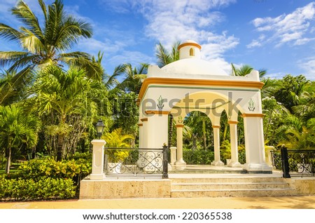 Wedding gazebo on one of Caribbean Islands, tall exotic palm trees and blue sky. - stock photo