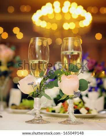 Wedding glasses with champagne and roses.