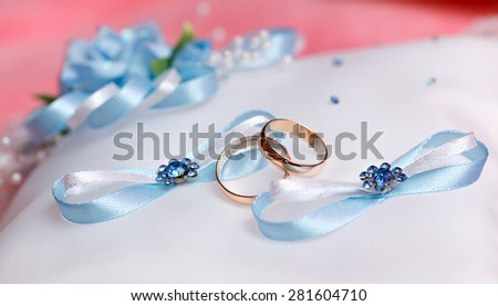 Wedding gold rings bride and groom on decorative pillow. - stock photo