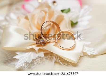 Wedding gold rings bride and groom on decorative pillow.