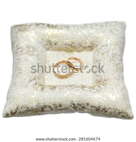 Wedding gold rings bride and groom on decorative pillow. Isolated.