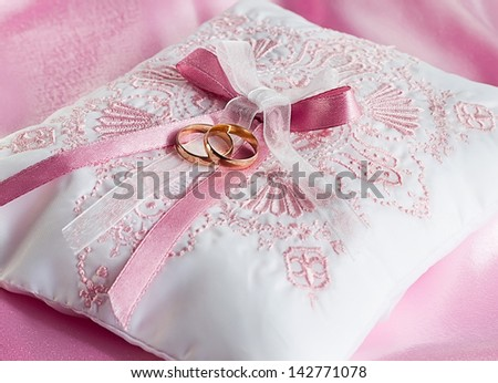Wedding gold rings on a pillow on pink - stock photo