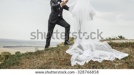 Wedding. Groom and bride on hill. Symbol of togetherness. Very long veil.  - stock photo