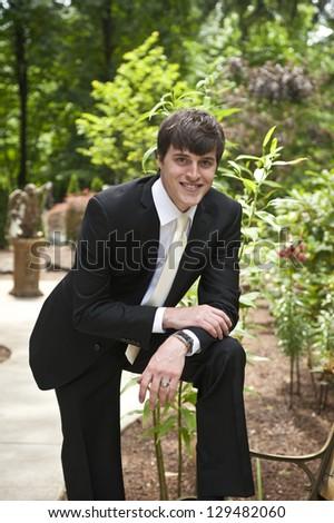 Wedding groom resting elbow on knee in park - stock photo