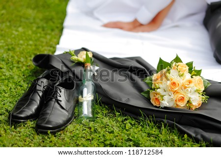 Wedding groom's shoes, jacket, bouquet, a reference in a bottle in the background the bride and groom hands, focused to bouquet - stock photo