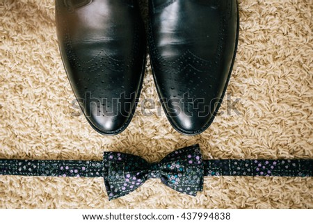 Wedding. groom shoes. Artwork. Grain. Leather shoes groom standing next to a black bow tie - stock photo