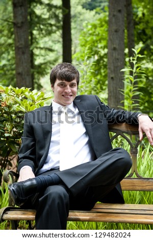 Wedding groom sitting on bench in park - stock photo