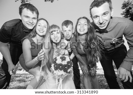 Wedding group of friends. Bride and groom with friends. Black and white image. Just married. Group of young friends make selfie photo with smart phone camera in wedding day. Funny people on the park. - stock photo