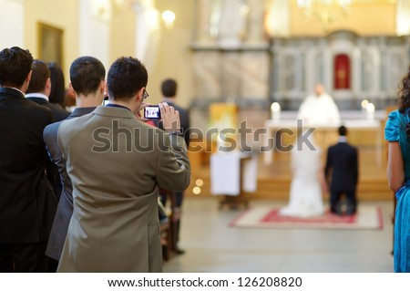Wedding guest taking photos on a wedding ceremony - stock photo