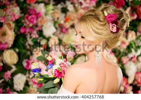 Wedding hairstyle a young girl. Bride. Woman with Flowers in her hair. High stacking, a bundle of curls. Beautiful blonde model. Earrings and bouquet - stock photo