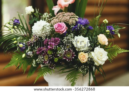 Wedding hall decorated with beautiful floral bouquet. Floral compositions with fresh roses, asters and  fern leaves. - stock photo