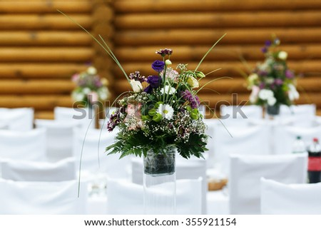 Wedding hall decorated with beautiful floral bouquets. Floral compositions with fresh roses, asters and  fern leaves. - stock photo