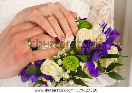 wedding hands with rings and bouquet - stock photo
