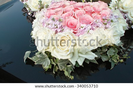 wedding heart shape bouquet with rose bush, Black car with a delicate bouquet of roses. Wedding car decoration.  - stock photo