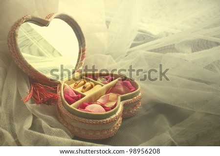 Wedding heart-shaped box with rings and rose petals - stock photo