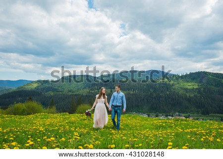 wedding in mountains, a couple in love, mountains background, standing surrounded dandelions, among the lawn with the green grass, rustic style, girl in long tulle dress, romantic landscape, walking